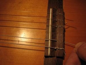 Potegni struno skozi luknjico na spodnji strani kitare
